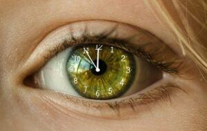 A green eye with the hands of a clock