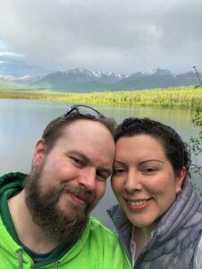Jessica and husband in front of lake in Alaska.