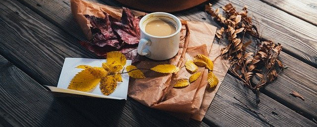 Table with coffee and dried yellow, red and brown leaves